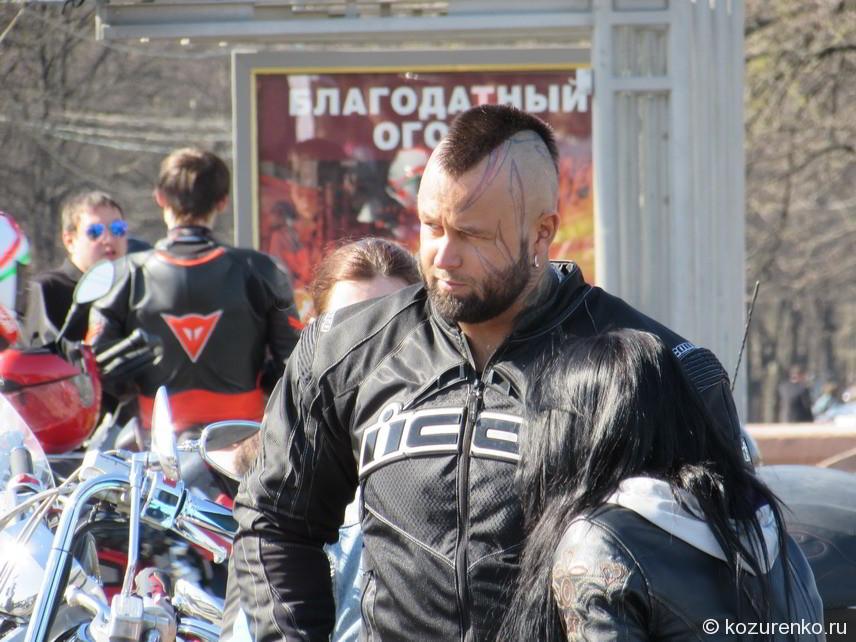 Байкер с татуировками на голове и лице. Серьезный тип.