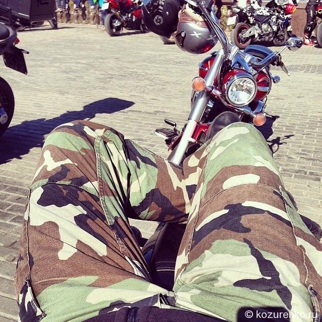 Кот Мартовский лежит на своем мотоцикле
